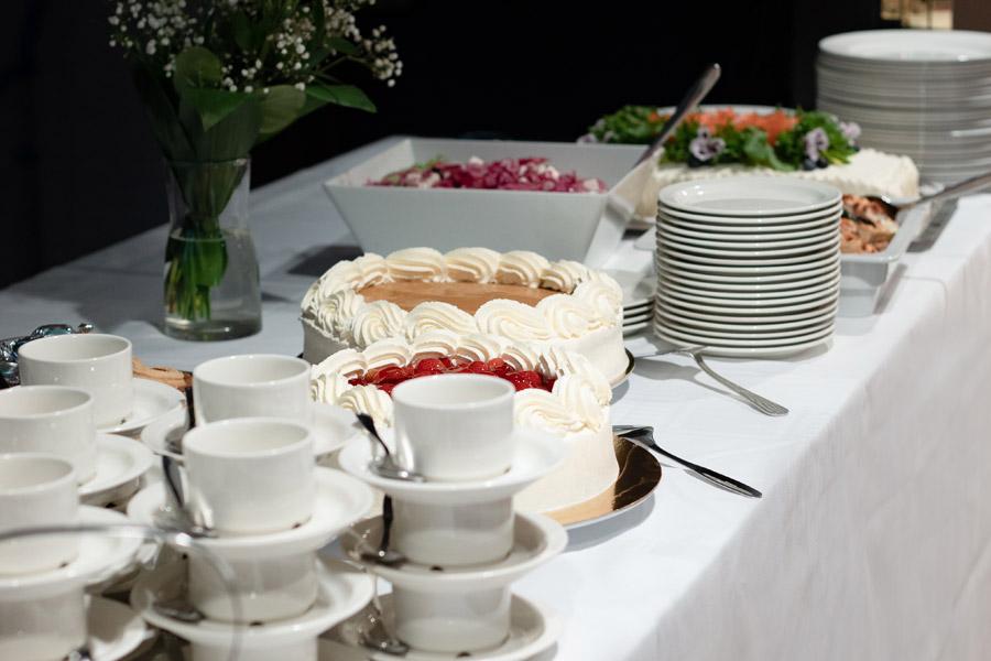 Kahvipöytä, jossa tarjolla voileipäkakkua, piiraita, salaattia ja kakkuja.